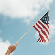 Photo of a hand waving a small American flag